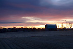 Idaho, south central, Hagerman. A color sunrise and stone foundation barn in winter.