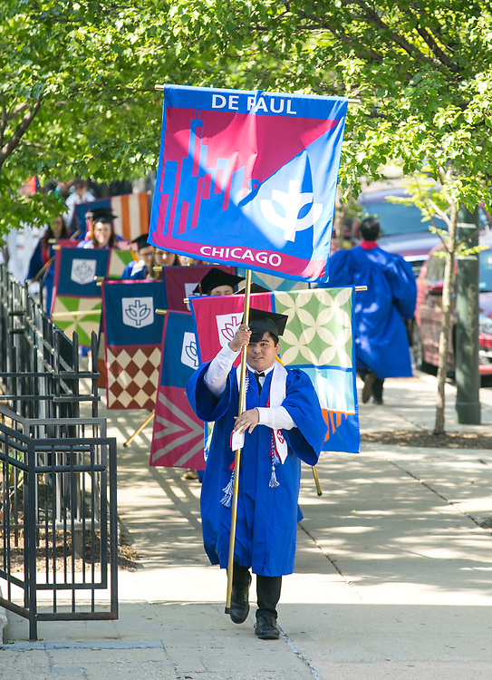 Students carrying the individual college flags make their way to the Saint Vincent de Paul Parish Church on DePaul University's Lincoln Park Campus for the annual Baccalaureate Mass Friday, June 9, 2017. The event was part of the 119th commencement ceremonies for the Chicago university. (DePaul University/Jamie Moncrief)
