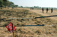 "Angola. Cuando Cubango. Mavinga. The death's-head sign says ""Watch for mines, Danger"".  Mines (personal, anti tanks,..) are laid in the field. Soldiers walk on the sandy roadtrack. © 2002 Didier Ruef"