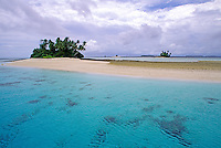 A tiny white sand beach with a lone stand of palm trees rises from the clear blue Pacific Ocean on Mili Atoll in the Marshall Islands. Fluffy white clouds highlight the background.