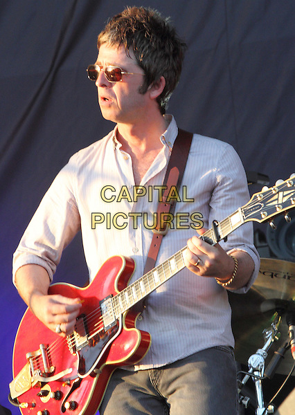 Noel Gallagher of Noel Gallagher's High Flying Bird's.V Festival 2012 - Day One, Hylands Park, Chelmsford, Essex, England..August 18th 2012.on stage in concert live gig performance music half length grey gray shirt sunglasses shades guitar profile  .CAP/JIL.©Jill Mayhew/Capital Pictures