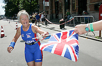 01 JUL 2007 - COPENHAGEN, DEN - Carol Killick ,silver medallist in the Womens 60-64 age group, takes a Union Jack flag from a supporter as she nears the finish line - European Age Group Triathlon Championships. (PHOTO (C) NIGEL FARROW)