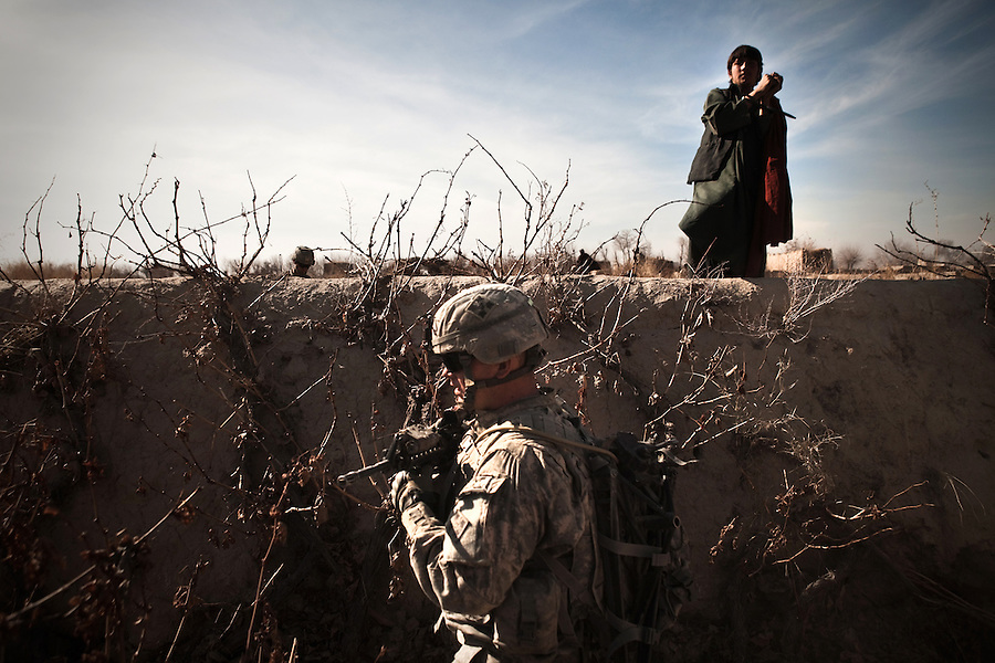 A soldier with Charlie Co. 1st Battalion 12th Infantry Regiment, 4th Infantry Division leads a man suspected of being a Taliban fighter during a patrol in Zhari District, Kandahar, Afghanistan. The violently contested district sits astride the strategically Highway 1 ringroad between Kandahar and Lashkar Gah and is seen by some as the birthplace of the Taliban movement.