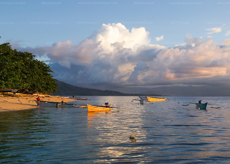 Siladen Island has one resort and a small village, which has one hotel.  Each night, villagers' boats can be seen glowing in the sunset light off the village beach.  The land in the distance is North Sulawesi.  (In the Bunaken National Park off North Sulawesi, Indonesia.)