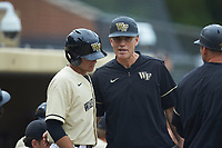 Wake Forest Demon Deacons head coach Tom Walter (16) gives instructions to Michael Turconi (6) during the game against the Miami Hurricanes at David F. Couch Ballpark on May 11, 2019 in  Winston-Salem, North Carolina. The Hurricanes defeated the Demon Deacons 8-4. (Brian Westerholt/Four Seam Images)