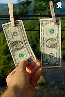 Man touching one US dollars banknote hanging on clothesline, close-up of hand (Licence this image exclusively with Getty: http://www.gettyimages.com/detail/sb10065474bo-001 )