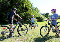 NWA Democrat-Gazette/DAVID GOTTSCHALK Instructor Cate Mertins (from left) reviews Monday, June 10, 2019, the proper technique of braking to Hattie Mertins, 10, and Annie Meldrum, 14, during the Mountain Bike Camp for Girls at the north shore of Lake Fayetteville. The week long camp for girls 8-11 years old is an introduction to mountain biking that includes learning basic trail skills riding, gaining confidence and developing a confident positive approach to cycling.
