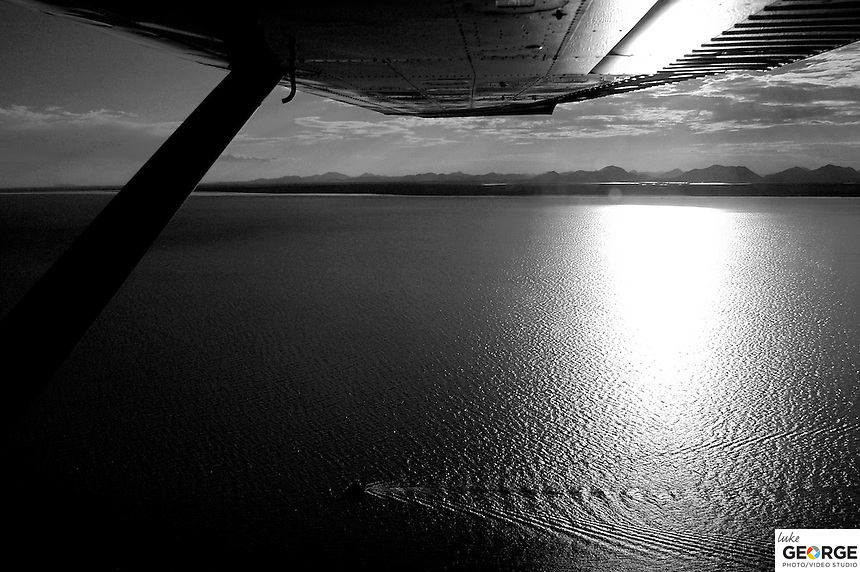 Nushagak Bay Alaska, flying from Dillingham to Ekuk with the Wood River Mountains in the distance and a drift boat fisherman in the bay.