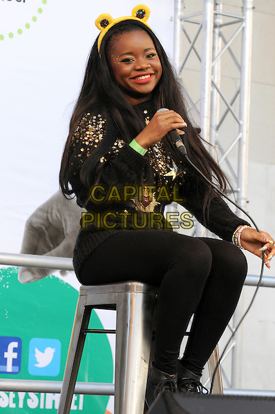 A*M*E (Amy Kabba).BBC Children In Need's Pudsey Street -photocall, New Piazza, Covent Garden, London, England..3rd November 2012.full length sitting black red lipstick ears on stage in concert live gig performance performing music boots .CAP/PP/BK.©Bob Kent/PP/Capital Pictures