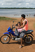 Altamira, Brazil. Young man with his daughter on a motorcycle beside the Xingu River.