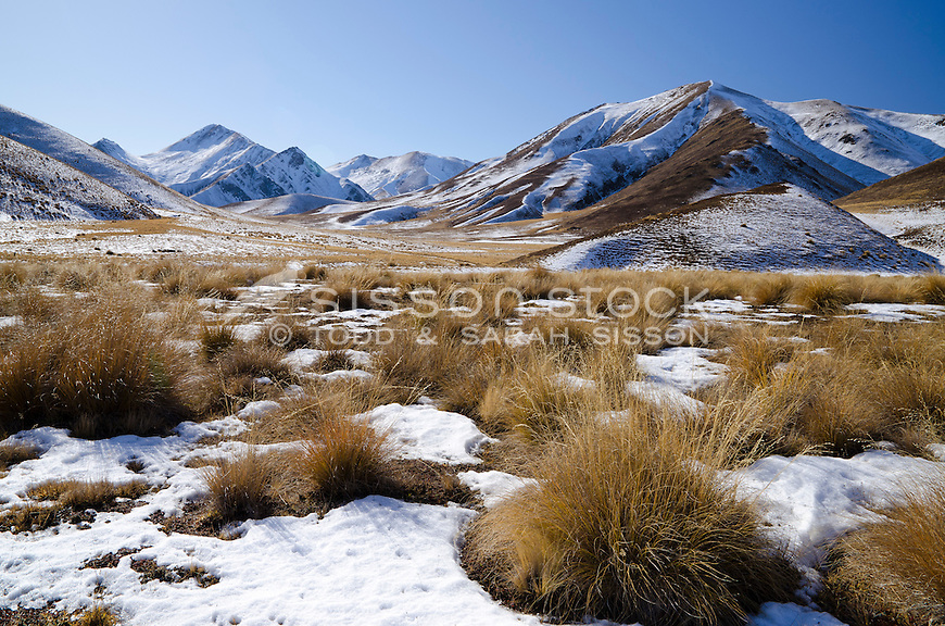 Snow covered hills and tussock grasses on a sunny winter day in the Lindis Pass, Central Otago, South Island