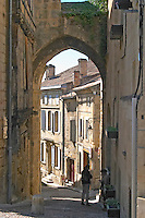 A street in the old medieval village of Saint Emilion, Bordeaux. one person walking on the street.