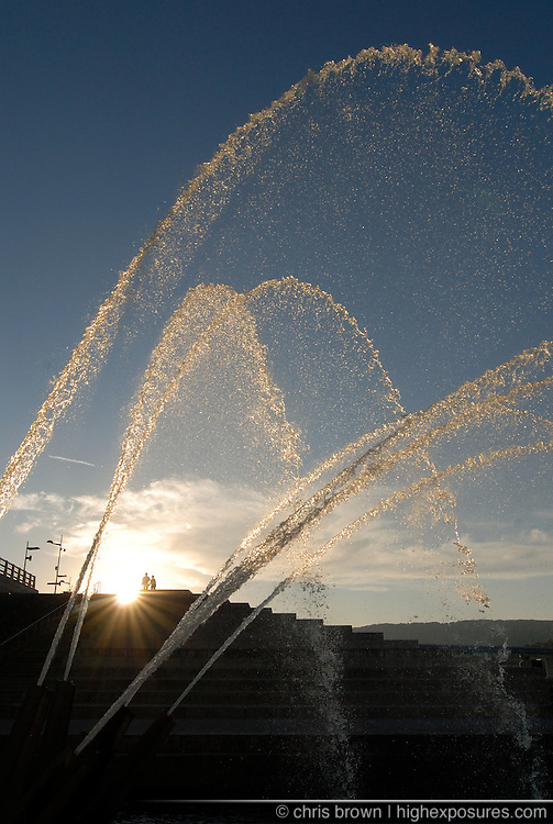 A man  and woman walk into the sunset near a fountain in downtown Chattanooga.