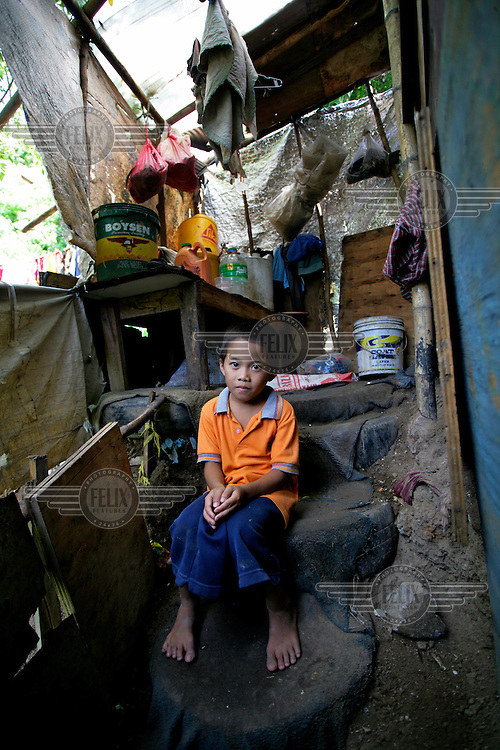 14 year old Rex outside his family home where he lives with his parents and nine siblings on the Olongapo Landfill site. He scavenges the site for up to ten hours a day looking for saleable items.