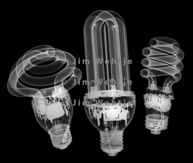 X-ray image of three compact fluorescent lamps (white on black) by Jim Wehtje, specialist in x-ray art and design images.