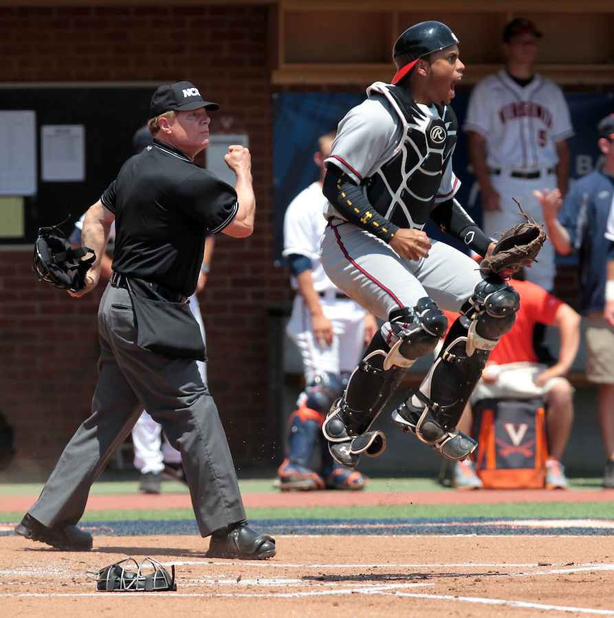 Maryland catcher Kevin Martir (32) reacts after tagging out Virginia outfielder Mike Papi (38) at home plate in the first inning of an NCAA college baseball tournament super regional game against Maryland in Charlottesville, Va., Saturday, June 7, 2014. Maryland defeated Virginia 5-4. (AP Photo/Andrew Shurtleff)