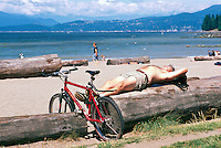 Man sunbathing at Beach, Stanley Park at English Bay, Vancouver, BC, British Columbia, Canada, Summer - West Vancouver and North Shore Mountains in background