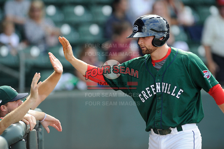 First baseman Sam Travis (28) of the Greenville Drive, right, is congratulated in the dugout after hitting a home run in a game against the Savannah Sand Gnats on Sunday, August 24, 2014, at Fluor Field at the West End in Greenville, South Carolina. Travis is a second-round pick of the Boston Red Sox in the 2014 First-Year Player Draft out of Indiana University. Greenville won, 8-5. (Tom Priddy/Four Seam Images)