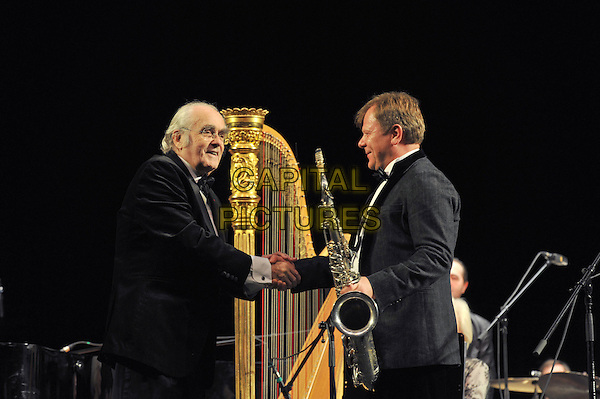 "Michel Legrand, Igor Butman.Concert in the Hall ""October"", St. Petersburg, Russia..February 1st, 2012.in concert on stage live gig performance performing music half length black tuxedo saxophone side profile shaking hands .CAP/PER/VB.©VB/PersonaStars/Capital Pictures."