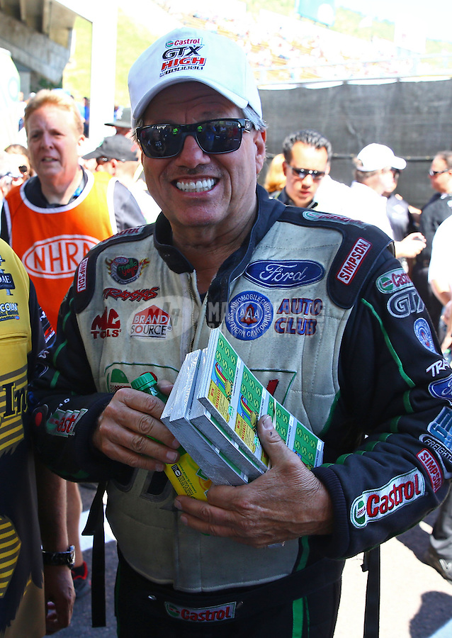 Jul. 21, 2013; Morrison, CO, USA: NHRA funny car driver John Force holds 1000 dollars worth of lottery scratchers during the Mile High Nationals at Bandimere Speedway. Mandatory Credit: Mark J. Rebilas-