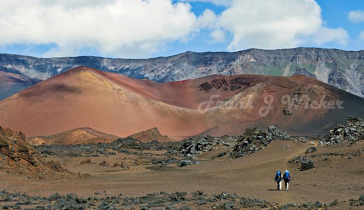 Two hikers and Ka Moa O Pele cinder cone in HALEAKALA NATIONAL PARK on Maui in Hawaii USA