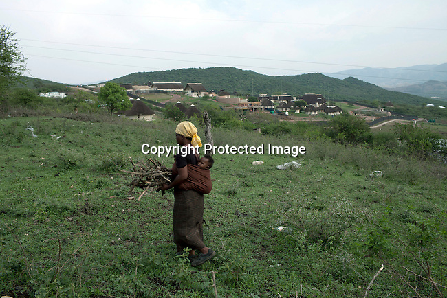 NKANDLA, SOUTH AFRICA - OCTOBER 10: A lady carries firewood that she collected close to South Africa president Jacob Zuma's new private residence in his birth village on October 10, 2012 in KwaNxamalala, Nkandla. South Africa.  The South African government is spending R240-million (about US$ 27 million) to construct the vast property for his large family. (Photo by Per-Anders Pettersson)
