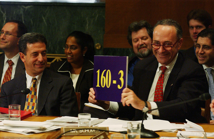 10/2/03.PICKERING NOMINATION--Sen. Charles E. Schumer, D-N.Y., holds up a sign for Sen. Richard J. Durbin, D-Ill., showing the number of judges approved versus the number blocked, during the Senate Judiciary business meeting to consider the nomination of Charles W. Pickering Sr. to be U.S. Circuit judge for the 5th Circuit. Sen. Russell D. Feingold, D-Wis., looks on. The committee endorsed the nomination with a 10-9 party-line vote, setting the stage for yet another Democrat filibuster over President Bush's judicial selections..CONGRESSIONAL QUARTERLY PHOTO BY SCOTT J. FERRELL