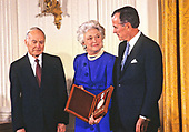 United States President George H.W. Bush and first lady Barbara Bush present the National Medal of Arts to American sculptor and teacher Walker Hancock during a ceremony in the East Room of the White House in Washington, DC on November 19, 1989. <br /> Credit: Ron Sachs / CNP