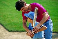 Father or coach helps boy aged 10-12 with batting stance in baseball training. father and son or coach and little leaguer.