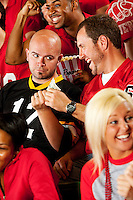 Multi-ethnic crowd of American football fans in a stadium, cheering, eating and having fun.