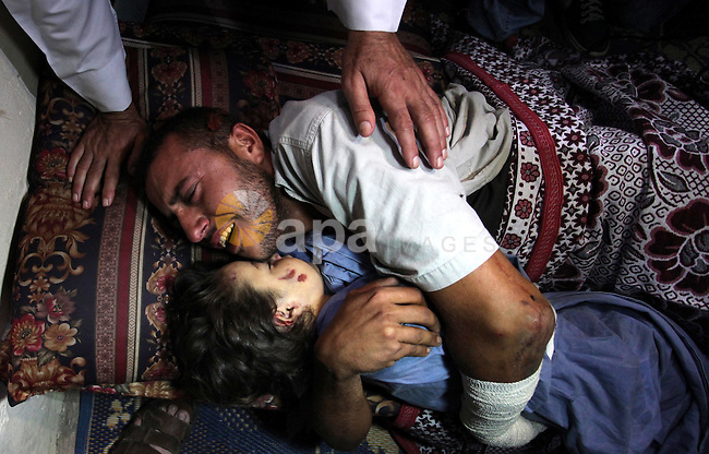 "Palestinian father Yehya Hasan mourns while holding the body of his daughter, Rahaf, during a funeral for the toddler and her pregnant mother on October 11, 2015, at the al-Nusairat refugee camp, in central Gaza Strip. A pregnant Palestinian mother and her two-year-old daughter were killed in the air strike in the Zeitun sector south of Gaza City while three others were still trapped under the ruins of a house, medical sources said. Israel said it had targeted ""two Hamas weapon manufacturing facilities"" in response to two rocket launches at Israel the day before. Photo by Ashraf Amra"