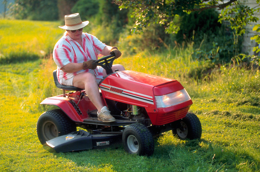 Woman on riding mower.