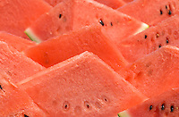 Red watermelon wedges at a market on a hot summer day.