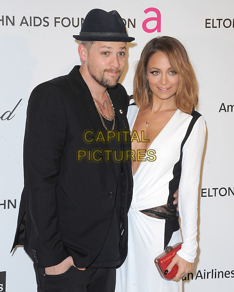 Joel Madden and Nicole Richie Madden.The 21st Annual Elton John AIDS Foundation Academy Awards Viewing Party held at The City of West Hollywood Park in West Hollywood, California, USA..February 24th, 2013.oscars half length black suit hat beard facial hair white dress long sleeves plunging neckline cleavage red clutch bag married husband wife.CAP/DVS.©DVS/Capital Pictures.