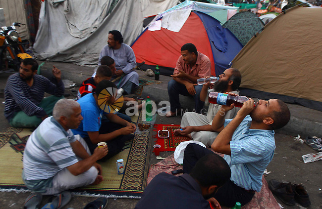 Supporters of the Muslim Brotherhood break their fast on the first day of Ramadan during a protest in support of ousted president Mohamed Morsi, outside Rabaa al-Adawiya mosque in Cairo, Egypt, 10 July 2013. Egyptian authorities have issued an arrest warrant for Mohammed Badie, the head of the Muslim Brotherhood, and nine other leading Islamists, on charges of inciting deadly violence earlier in the week, reported state media 10 July. At least 51 people, including an army officer, were killed in the clashes, raising the prospect of wider street violence in Egypt. Photo by Ahmed Asad