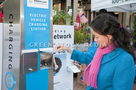 Woman looking at promotional display about the electric vehicle charging stations network infrastructure. The infrastructure needs to be built in order to support broad adoption of electric cars and the rechargeable lithium ion battery technology used in the Nissan Leaf. Nissan Leaf Zero Emission Tour promotional event for the Nissan Leaf electric car that is scheduled to be released in Fall 2010. Car specs from Nissan: 5 person capacity, 90 MPH top speed, lithium-ion battery, 100 mile average range per charge. Santana Row, San Jose, California, USA, 12/5/09