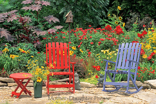 Colorful summer garden with bright red and blue rocking chairs on flagstone patio. Many whimsical artistiic touches to liven up the scene with statues, birdhouses, and cut flowers