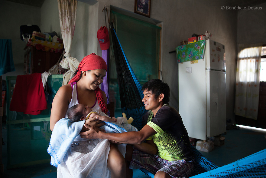"""Luz Betsaida Orozco Pineda and José Manuel Regalado López, her 17-year-old husband, with their new born baby at their home in Juchitán, Mexico on February 17, 2016. José Manuel gets up at3 amto collect scrap and fish; their home is around 15 minutes from the beach. He speaks little Spanish. Now 14, Luz became pregnant when she was 13 after being """"stolen"""" according to the Zapotec Indigenous tradition. Considered a traditional kind of marriage – Luz is too young to wed legally – the custom dictates that the couple go to the young man's house and announce their plans to marry. While the family waits, the couple go to a room together; he emerges later with a blood-stained handkerchief to prove his bride's virginity. Luz, who started going out with the father of her baby when she was 10, lives with her in-laws in the 6 de noviembre neighbourhood on the outskirts of Juchitán in the southern Mexican state of Oaxaca. Her baby was born on January 13, 2016. Despite following tradition, she speaks little Zapotec – the language of her husband and his family – she follows tradition, wearing a headscarf to protect her health as she is still observing the 40-days quarantine period after giving birth, during which she stays in the house. While Mexico has outlawed marriage under the age of 18, many young girls become unofficial wives and mothers much earlier. In Juchitán, teenage pregnancy is expected, even prized. Mexico ranks first in teenage pregnancies among the member countries of the Organization for Economic Co-operation and Development(OECD). Photo by Bénédicte Desrus"""