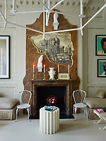 In the sitting room, a faux marble panel surrounds a real marble fireplace and an engraving of a Piranesi-style ruin is outlined in an irregular gilded frame whose shape echoes a Cocteau drawing. Resin falcons are painted white to mimic porcelain and a pair of Warholesque portraits by the artist Skid Stewart hang over a daybed.