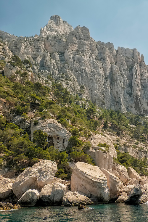 Raising up from the Mediterranean Ocean, towering limestone cliffs dominate the Les Calanques coastline in southern France.