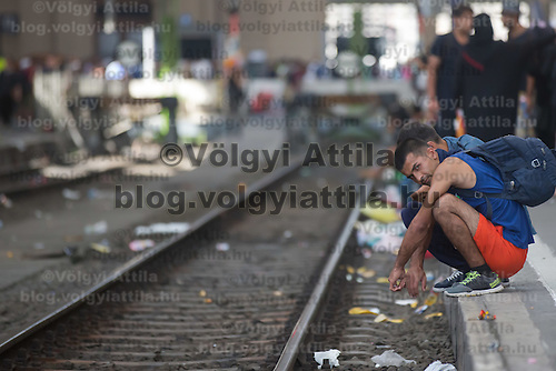 Illegal migrants sits on the platform edge as they wait to board a train in hopes to leave for Germany at the main railway station Keleti in Budapest, Hungary on September 03, 2015. ATTILA VOLGYI