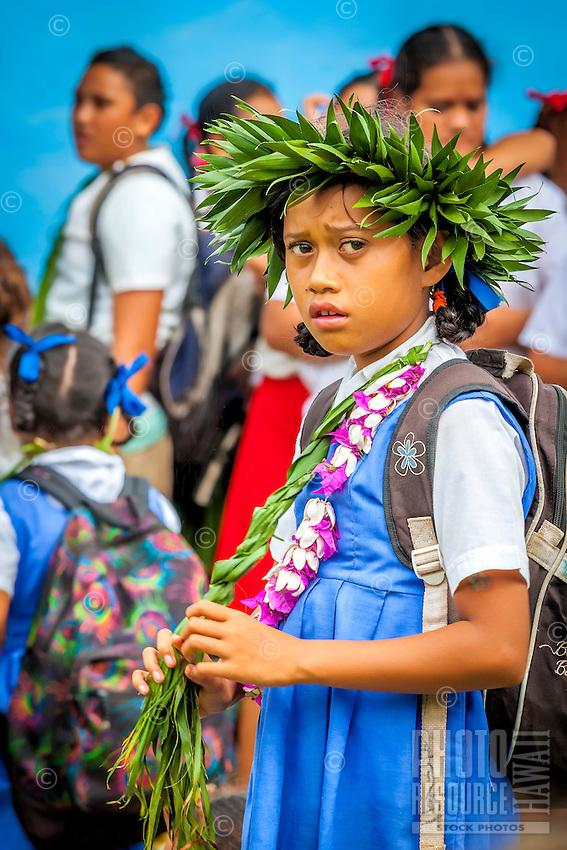 A young girl with flower and ti leaf adornments during Makirau Haurua's investiture with the Teurukura Ariki title, Aitutaki Island, Cook Islands.