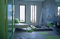 This concrete bathroom has a sunken bath and is dominated by an apple green cupboard