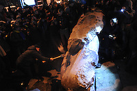 A protester shatter the fallen statue of Lenin with  a sledge-hammer