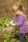 Toddler outside with bleeding heart plant.
