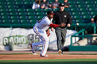 Rochester Red Wings first baseman Kennys Vargas (30) flips the ball to first base as first base umpire Travis Godec watches the play during a game against the Pawtucket Red Sox on May 19, 2018 at Frontier Field in Rochester, New York.  Rochester defeated Pawtucket 2-1.  (Mike Janes/Four Seam Images)