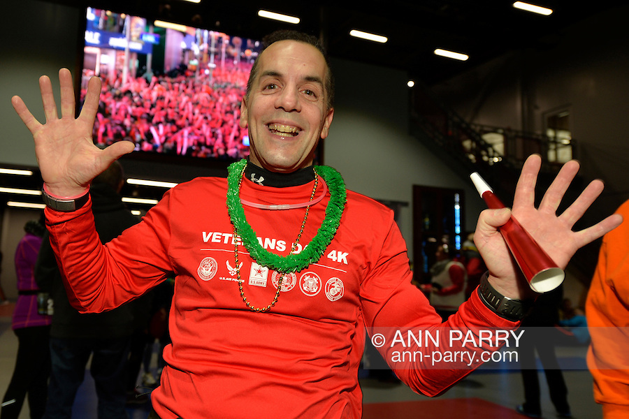 East Meadow, New York, USA. December 31, 2014. EDWARD MARIAN, of Huntington Station, in front of a large screen showing the crowd at Times Square NYC, is a runner who will participate in a 5K New Year's Eve DASH to support the Long Island Council on Alcoholism and Drug Dependence (LICADD) at the Twin RInks Ice Center at Eisenhower Park in Long Island. Marian ran in 80 races in 2014. A Skatin' New Year's Eve event started hours earlier and a New Year's Eve Party, open to runners, family and friends continued until 2:30 a.m.