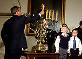 United States President George W. Bush returns the Shamos candle to the menorah as 6 year-olds Jacob Murphy and Sidney Hallem look on during the menorah lighting ceremony at the White House in Washington, DC on December 22, 2003.<br /> Credit: Ron Sachs / CNP