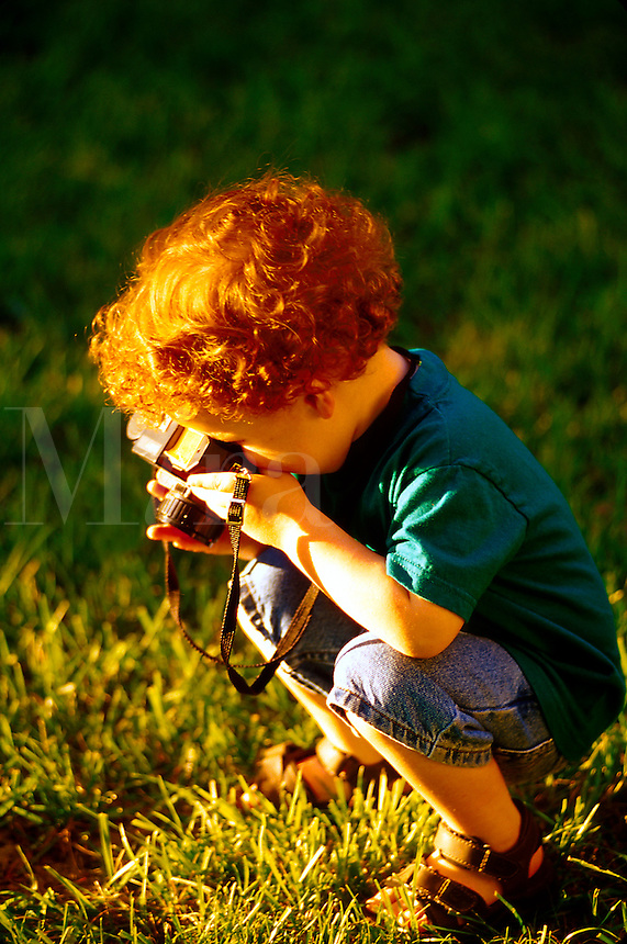 Portrait of a young boy with curly red hair, squatting down in the grass, playing at taking a picture with his toy camera.