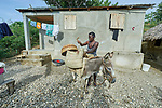 Ceneprise Etienne loads her donkey in front of her family's new home in Djondgon, a village near Jean-Rabel in northwestern Haiti. The family's previous house was destroyed during Hurricane Matthew in 2016, and Church World Service, a member of the ACT Alliance, helped the family build their sturdy new home. CWS also gave a donkey to the family, an animal that provides critical assistance in getting crops to market and fetching water for the family.